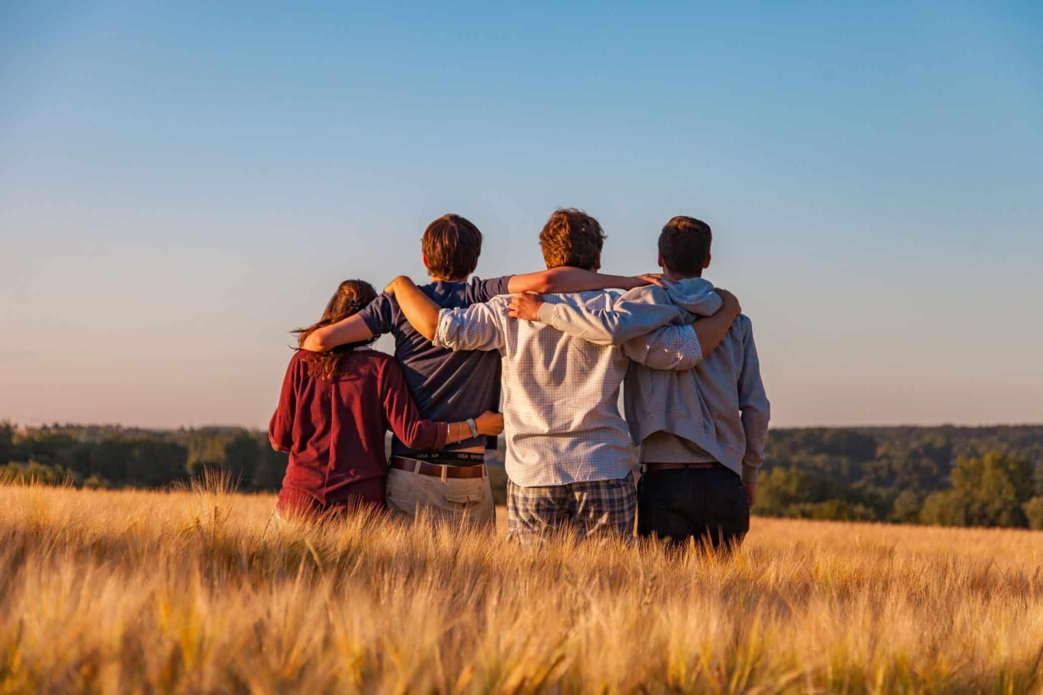grupo de amigos abrançando na planicie de trigo por do sol o que fazer na quarentena